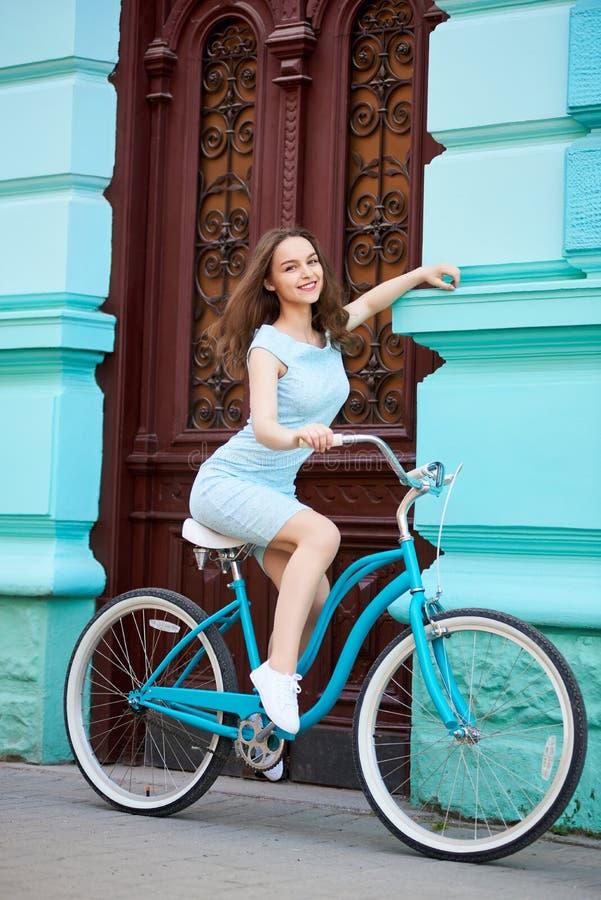 减速火箭的自行车的可爱的夫人在老大厦背景  库存照片