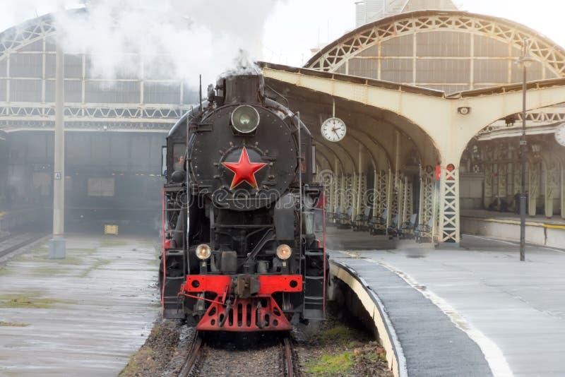 减速火箭的蒸汽火车离开与时钟的火车站在平台 库存图片