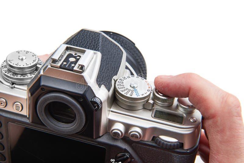 减速火箭的被称呼的数字式SLR照相机在被隔绝的手上 免版税图库摄影