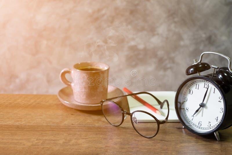 减速火箭的警报黑色时钟葡萄酒样式特写镜头与空白的开放书,红色铅笔和玻璃杯子咖啡粉红彩笔老 图库摄影