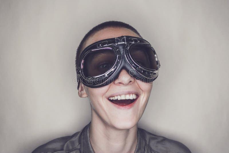 减速火箭的试验玻璃的愉快的女孩在灰色 免版税库存图片