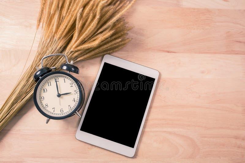 减速火箭的闹钟和数字片剂智能手机在木背景 免版税库存图片