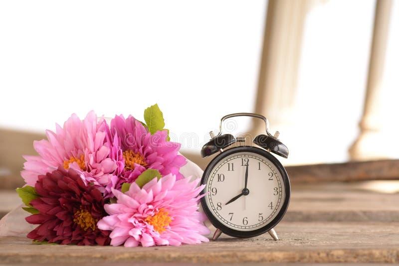 在木板条的减速火箭的闹钟和花花束 照片拍摄时间: february 01st, 2图片