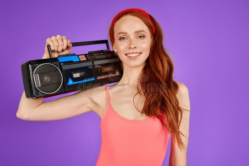 减速火箭的80s样式的姜女歌手posingwith便携式的音频球员 免版税图库摄影