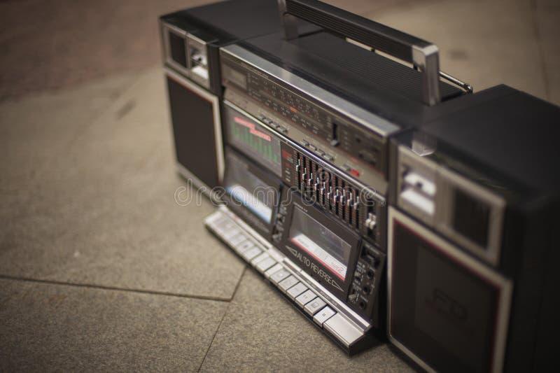 减速火箭的boombox,与一台盒式带录音机的一部过时的手提电话机从20世纪80年代,在边路的立场 斥责,臀部 免版税库存照片