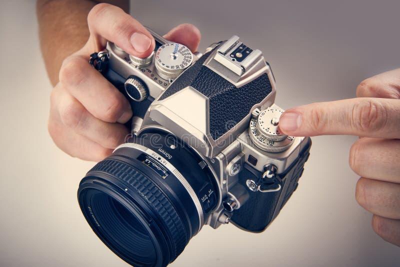 减速火箭的SLR照相机在摄影师特写镜头的手上 免版税库存照片