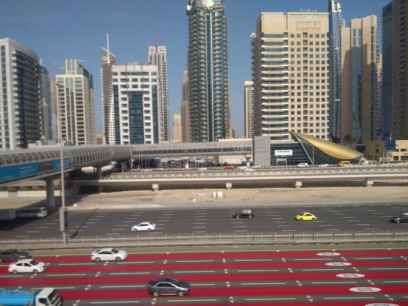 减速的红色asfalt在迪拜圆计划和cillindrical容量前面地铁和天际塔  免版税库存照片