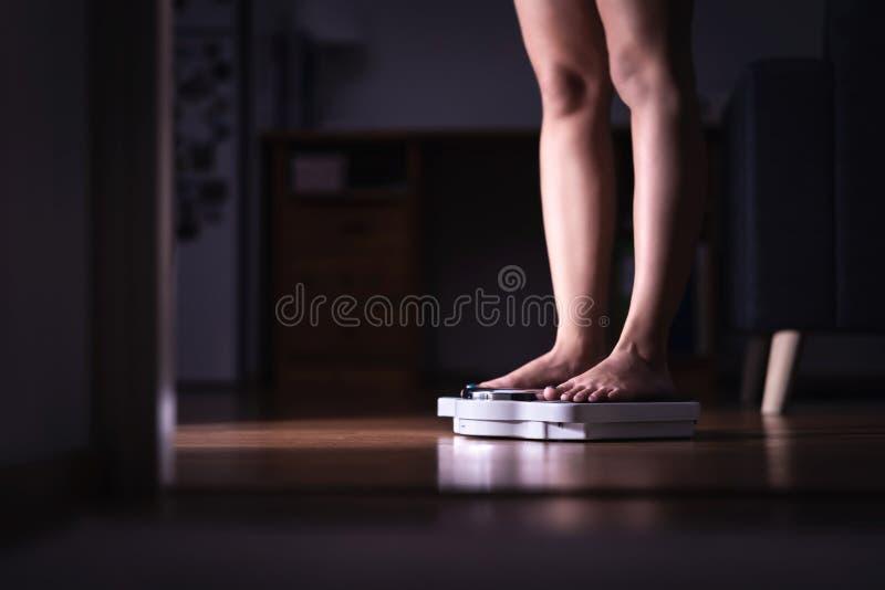 减重和饮食概念 站立在等级的夫人 称妇女的她自己 健身夫人节食 Weightloss和营养学 免版税库存照片