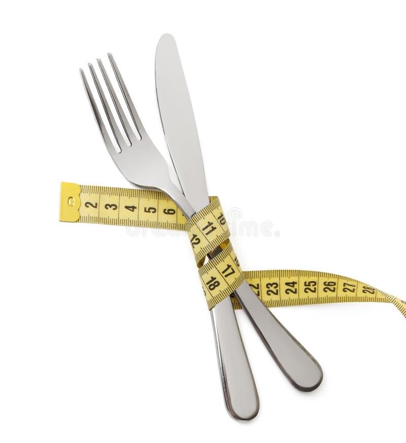 减重的日本人饮食 叉子和刀子在白色的黄色测量的磁带被包裹被隔绝的 免版税库存图片