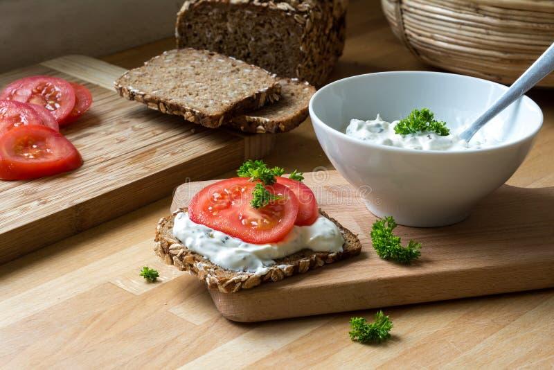 凝乳酪垂度用草本和土气整粒面包与toma 免版税库存图片