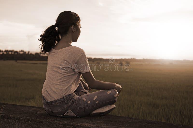 凝思和放松在Ricefield日落 免版税库存图片