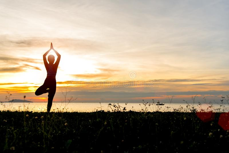凝思瑜伽生活方式在海日落的妇女剪影,放松重要 库存照片