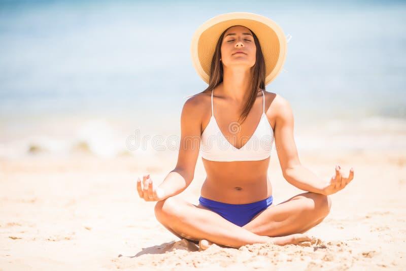 凝思 思考在平静的海滩的瑜伽妇女 放松在镇静禅宗片刻的莲花姿势的女孩在海洋水中在瑜伽h期间 免版税库存照片