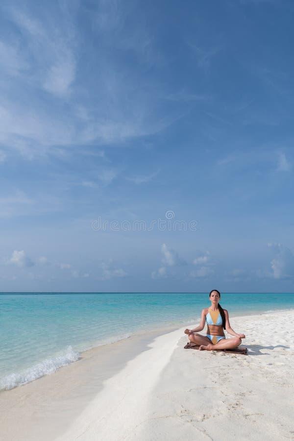 凝思-思考在平静的海滩的瑜伽妇女 免版税库存照片