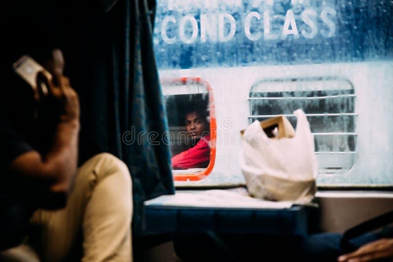 凝视从另一列火车的一个印度人,当下雨外面从豪拉连接点火车站在加尔各答,印度时 免版税库存照片
