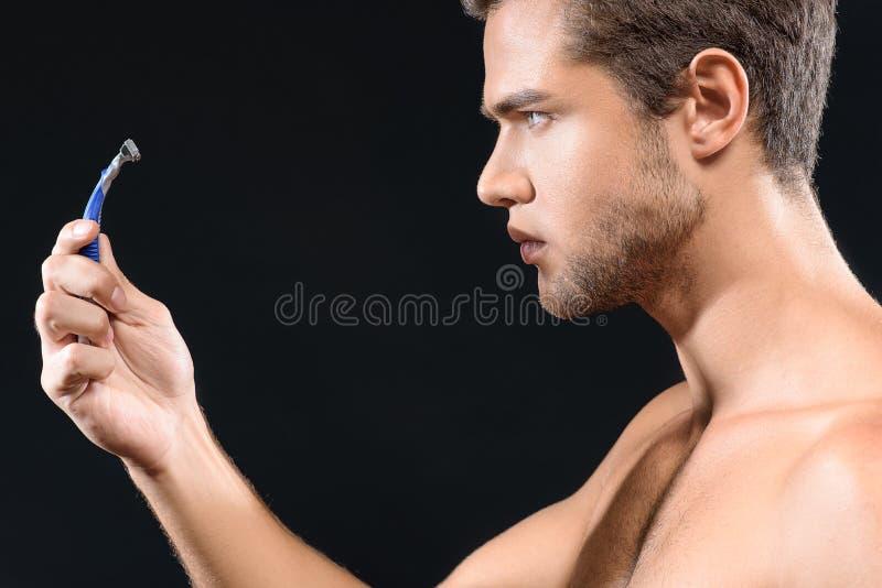 凝视剃具的体贴的人 免版税图库摄影