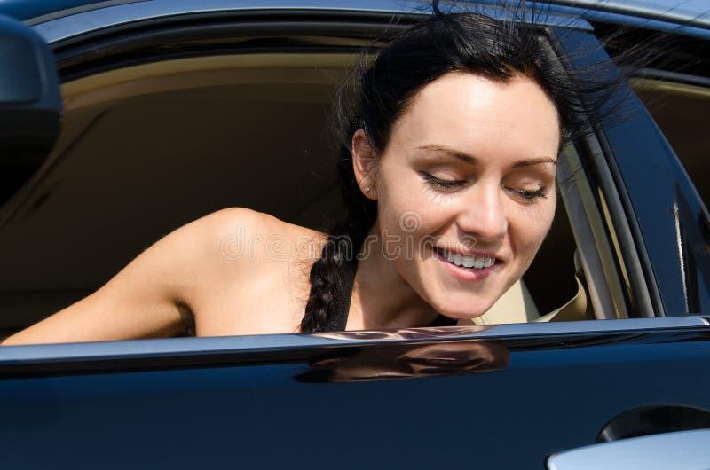 凝视在汽车外面的微笑的妇女 免版税库存照片