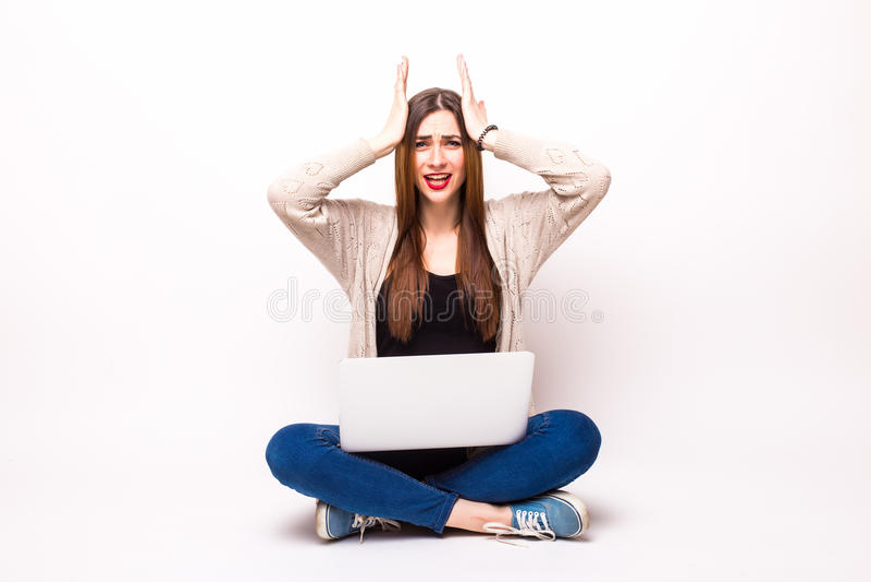 凝视她的膝上型计算机的一名随便加工好的年轻妇女的被隔绝的演播室射击 免版税库存照片