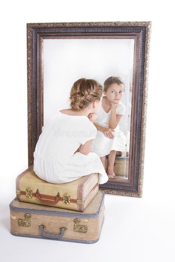 凝视她自己的孩子或女孩在镜子 库存照片