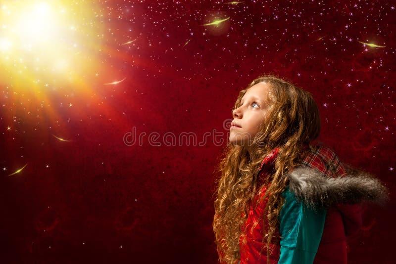 凝视明亮的阳光的逗人喜爱的女孩 免版税库存图片