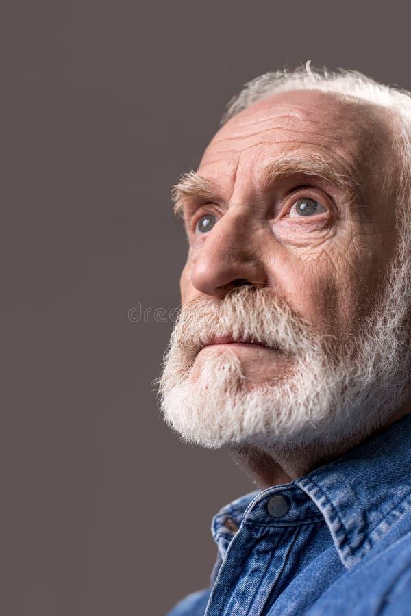 凝视沉思成熟的胡须半白的老人在旁边 免版税库存图片