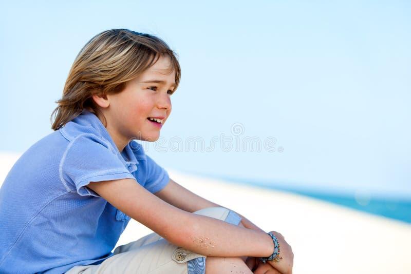 凝视海上的逗人喜爱的男孩。 库存图片