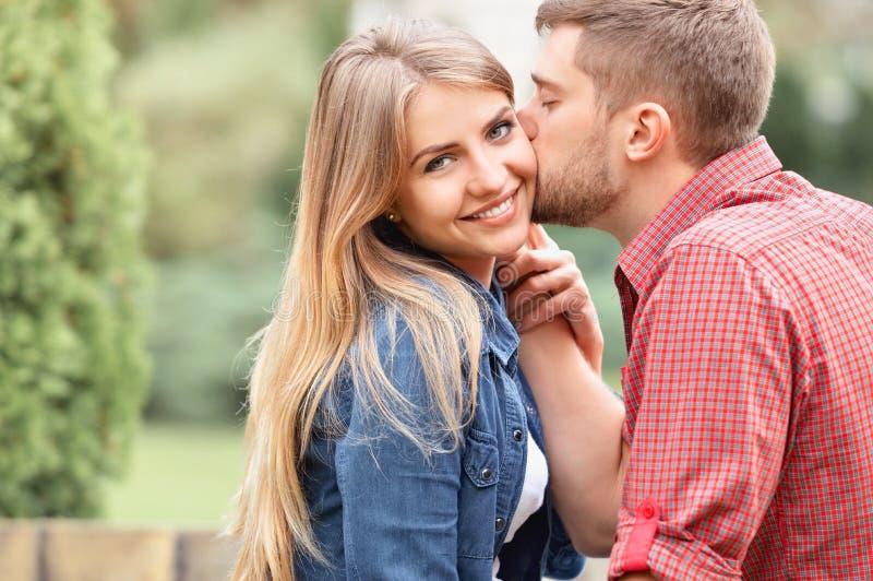 凝视照相机的年轻美丽的女孩,当被亲吻时 免版税库存照片