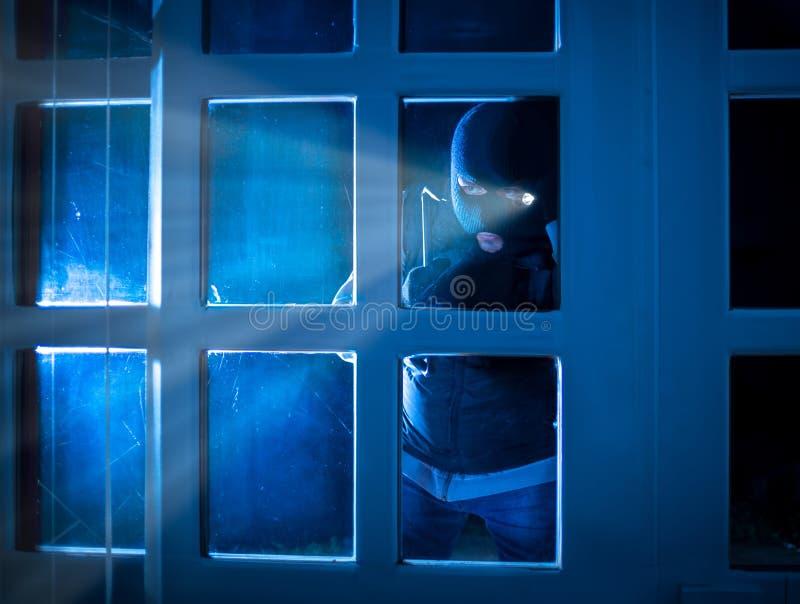 凝视的夜贼站立在黑暗外部和里面 免版税库存图片