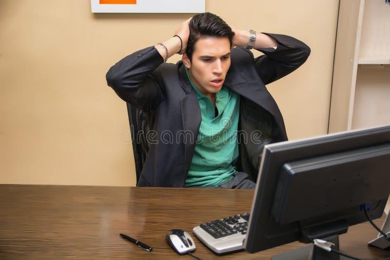 凝视计算机的出神的,担心的年轻人 免版税库存图片
