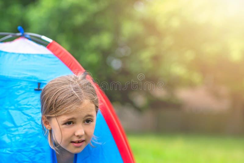 凝视通过帐篷开头的少女 免版税库存照片