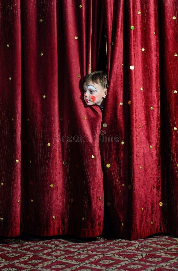 凝视通过阶段帷幕的男孩小丑 库存图片