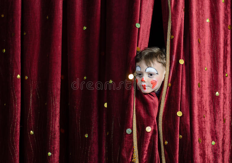 凝视通过阶段帷幕的男孩小丑 免版税图库摄影