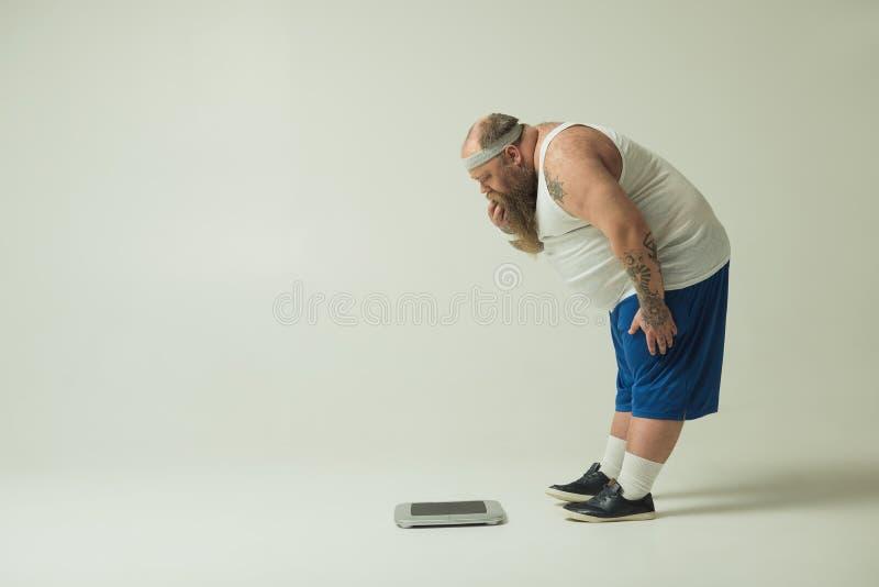 凝视重量标度的困惑的厚实的人 免版税库存图片