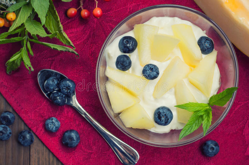 凝结用瓜、蓝莓和薄菏小树枝  木背景 顶视图 特写镜头 免版税库存图片