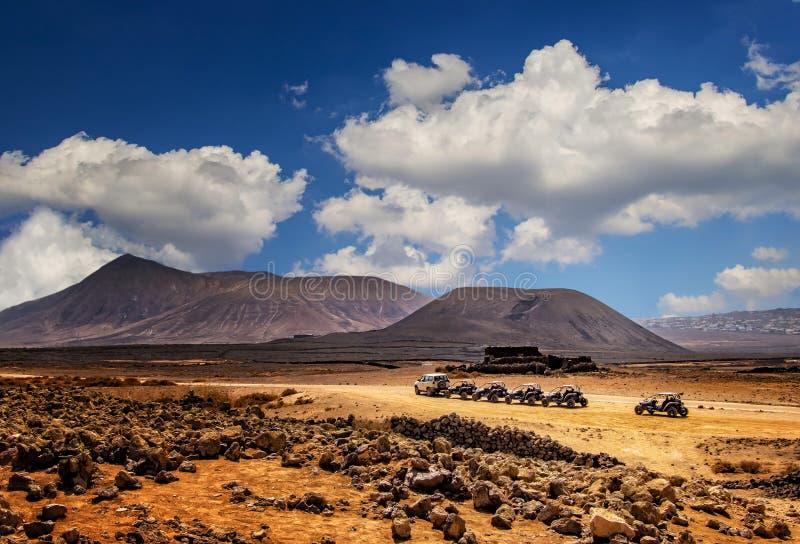 几个儿童车在美妙的沙漠风景的线 免版税库存照片