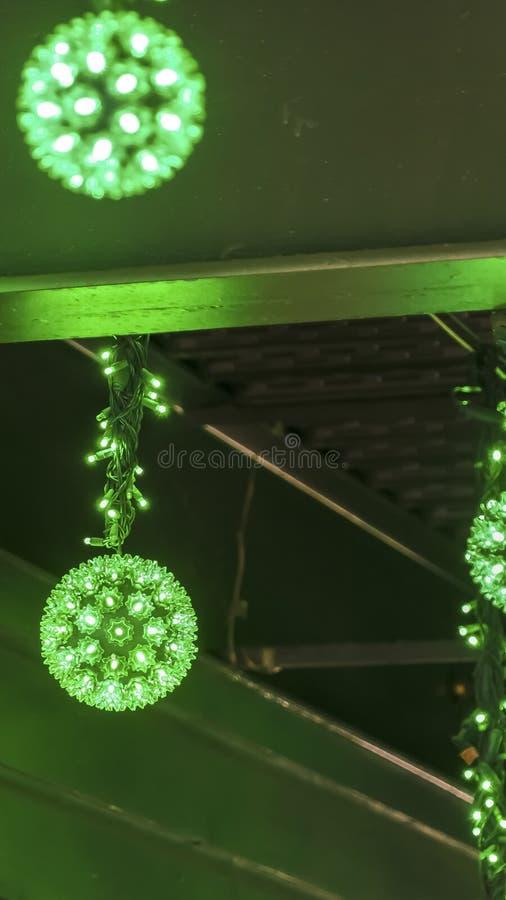 几个发光的霓虹绿灯球看法的垂直的框架关闭在晚上 免版税库存照片