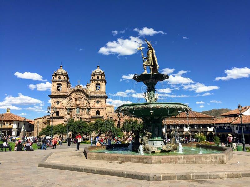 几个游人在美丽和古老库斯科,秘鲁敬佩阿马斯广场看法  免版税库存图片