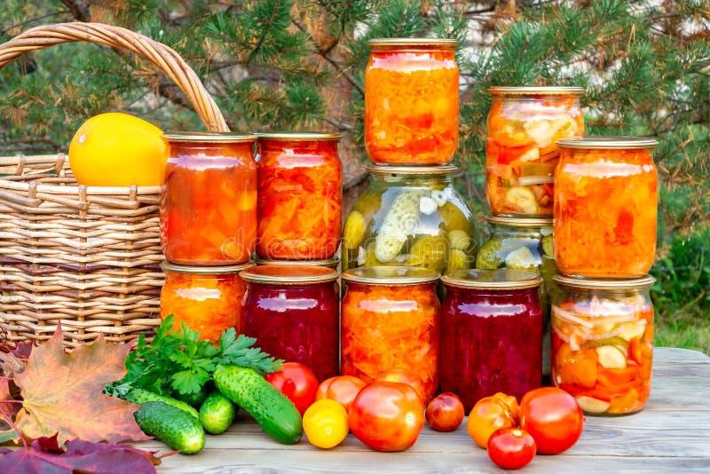 几个自创瓶子罐装菜和新鲜蔬菜在一张木桌-图象上 免版税库存图片