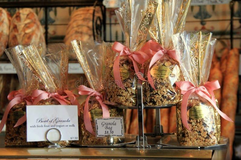 几个袋子做的格兰诺拉麦片,安置在柜台在新鲜的被烘烤的面包附近,夫人 伦敦` s面包店,萨拉托加,纽约, 2016年 库存照片