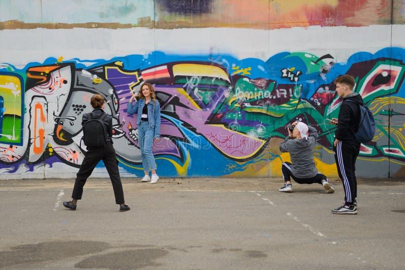 几位摄影师为墙壁的背景的一少女照相有街道画的 r ?? 免版税库存图片