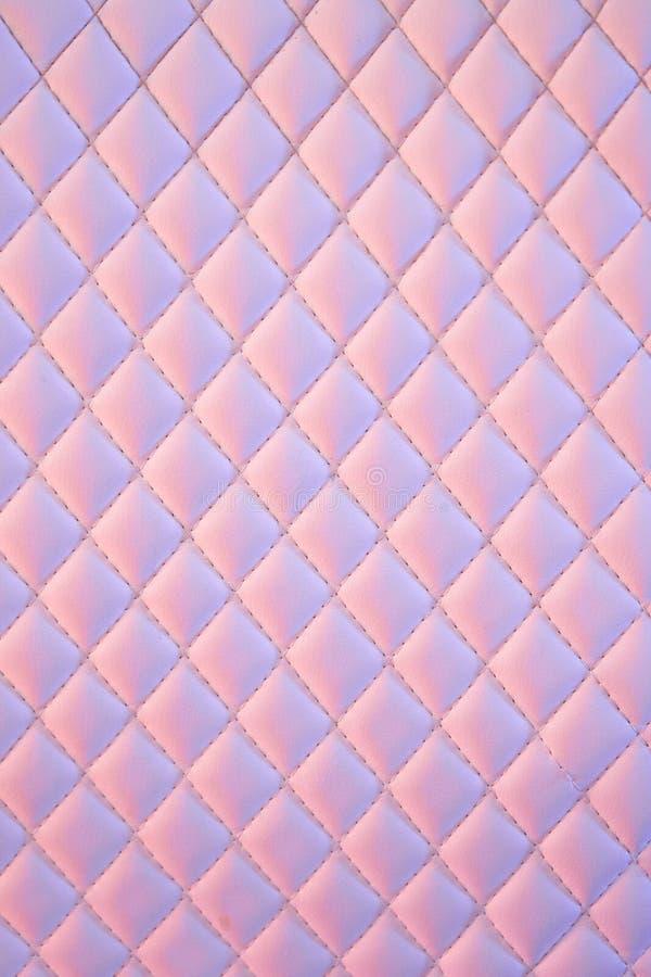 几何金刚石样式缝制了PU皮革在霓虹灯 库存图片