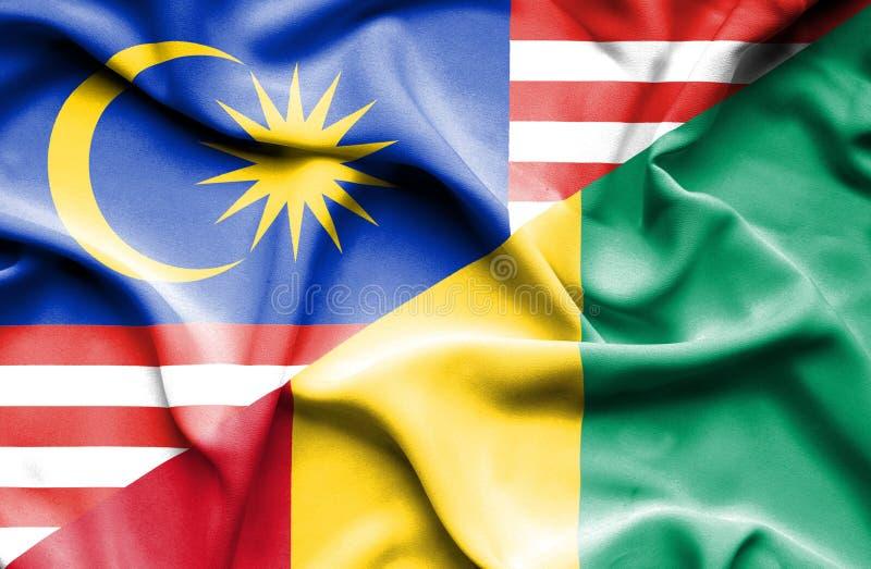 几内亚和马来西亚的挥动的旗子 库存例证