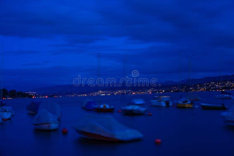 几条小船在利马特河河停住在苏黎世在晚上 免版税库存照片