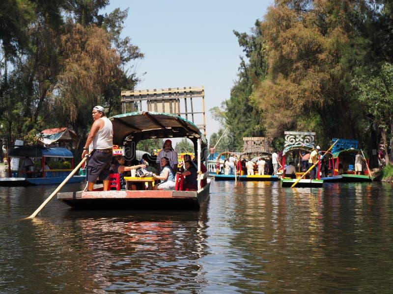几条色的墨西哥小船看法有游人和平底船的船夫的著名霍奇米尔科` s浮动庭院的在墨西哥 库存照片