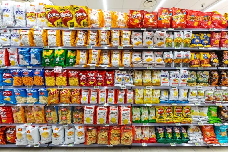 几盒芯片和快餐 用薯片不同的品牌的架子  免版税图库摄影
