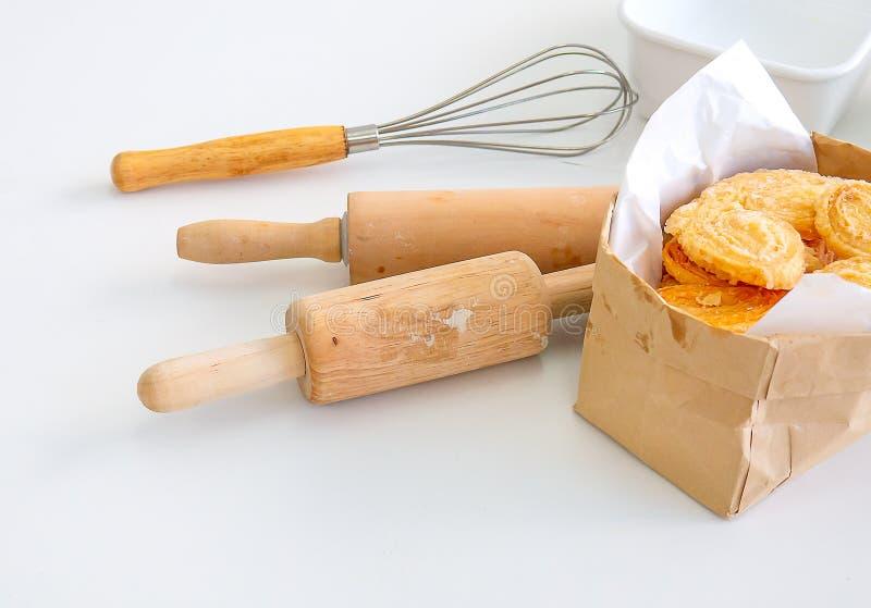 几设备或工具为烹调包括滚针、飞奔和碗或者杯子,全部的面包店在白色桌上把放 免版税库存照片