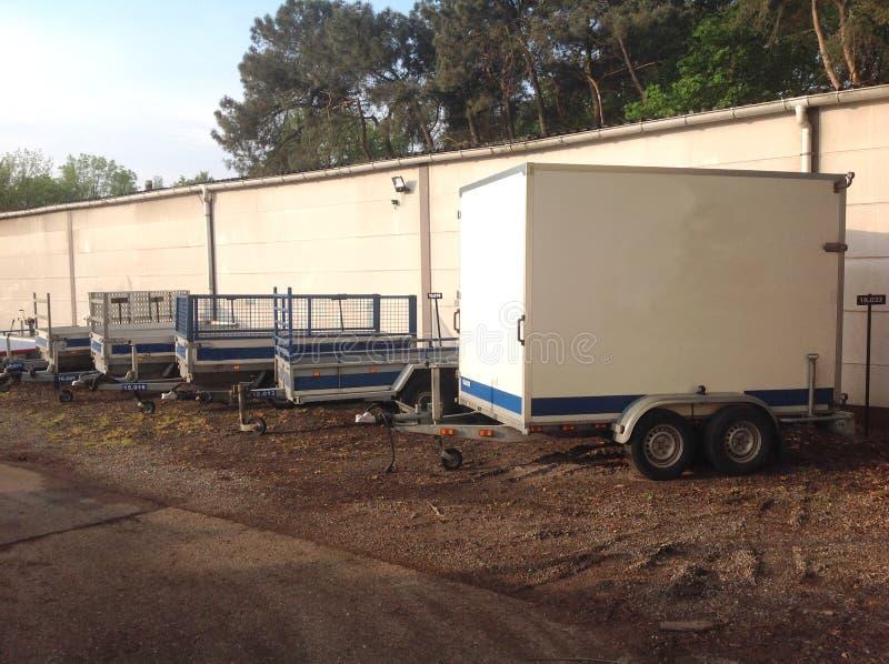 几辆拖车沿重的整体篱芭登上了 免版税库存照片
