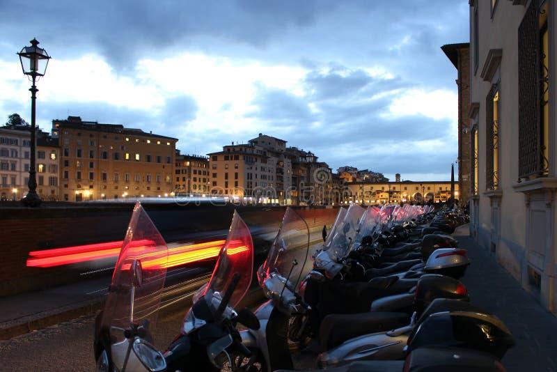 几辆摩托车沿有佛罗伦萨汽车和都市风景的轻的足迹的街道连续停放了  免版税库存图片