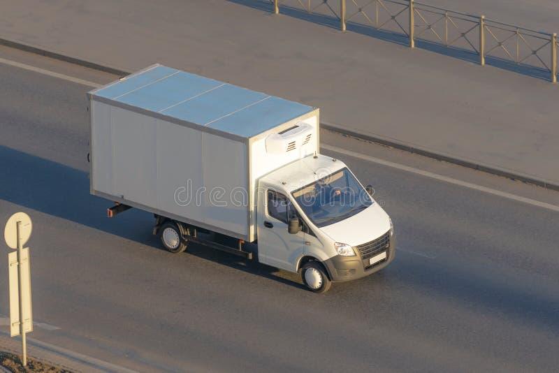 几驾驶在高速公路的送货车和白色后勤卡车 库存图片