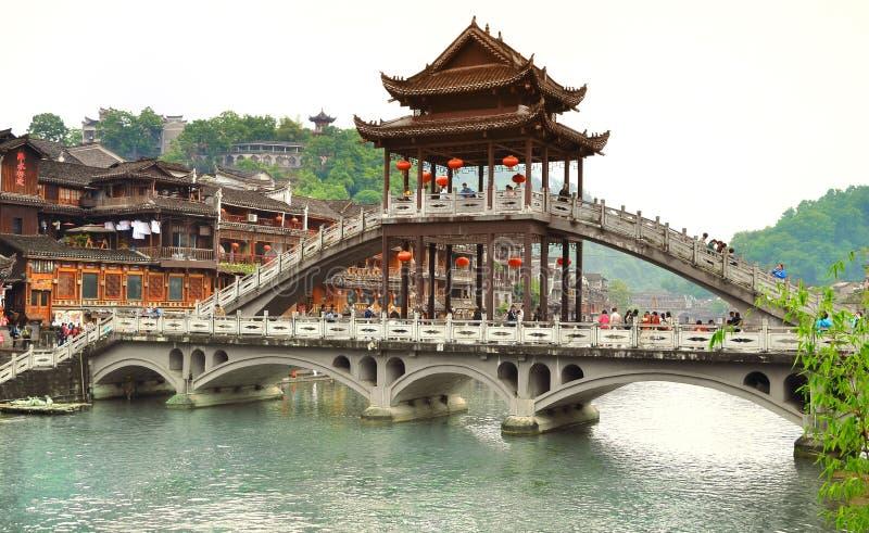 凤凰牌,中国- 2017年5月14日:在河沿附近的人们在凤凰牌的菲尼斯洪桥梁 库存图片